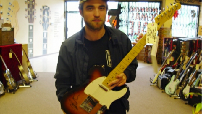 Robert Pattinson autographs guitar for the Midnight Mission